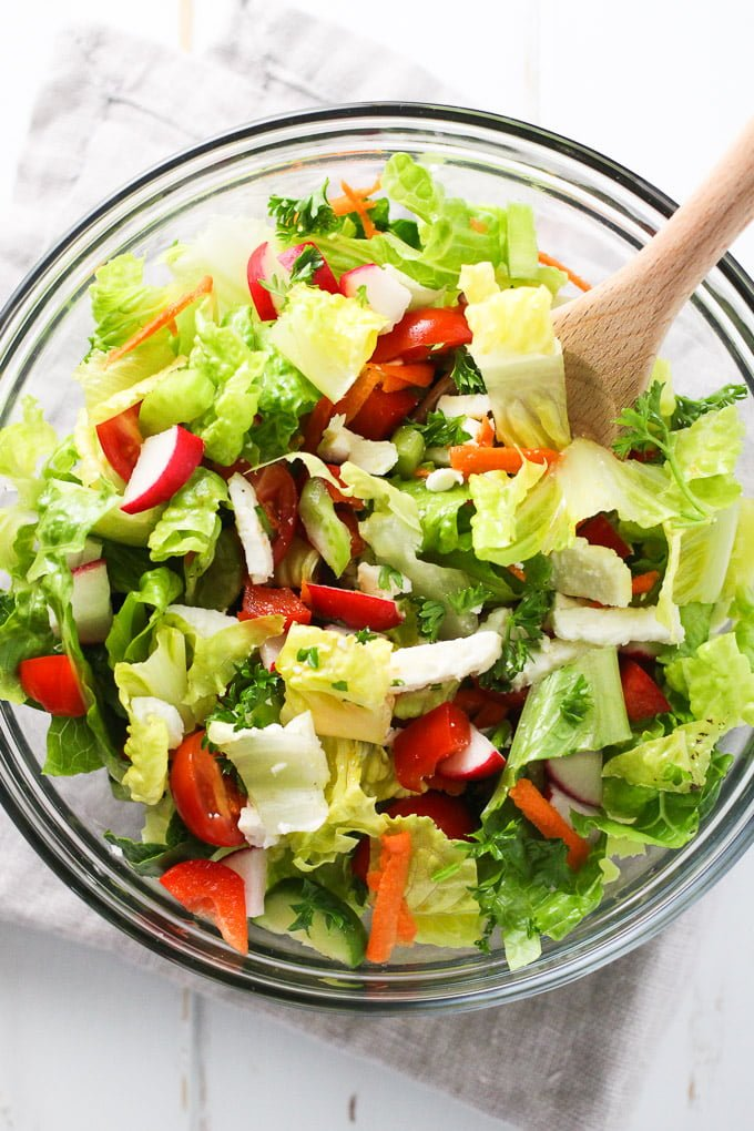 Romaine salad with chopped veggies and feta in a glass bowl. Top view.