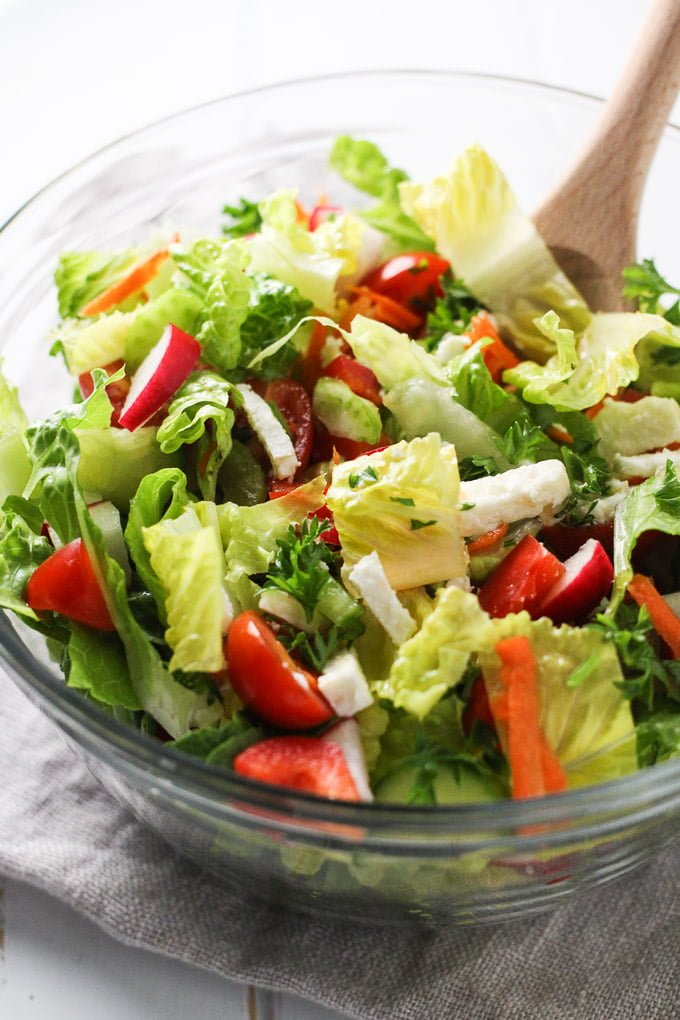 Romaine salad with chopped veggies and feta in a glass bowl.