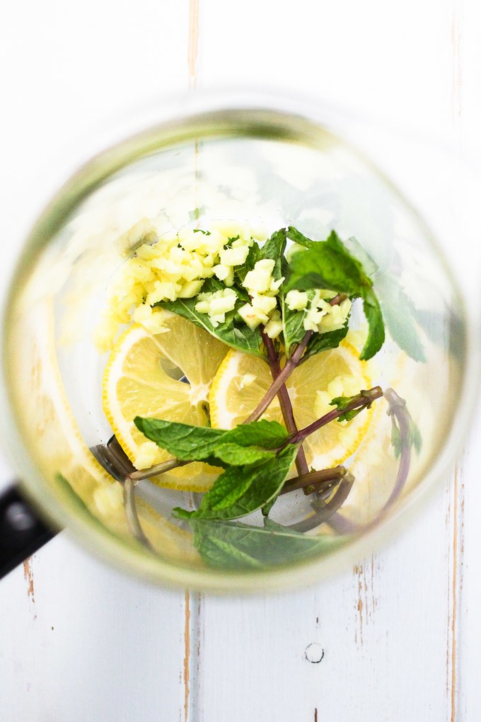 Minced ginger, mint leaves and lemon sliced in a French press.