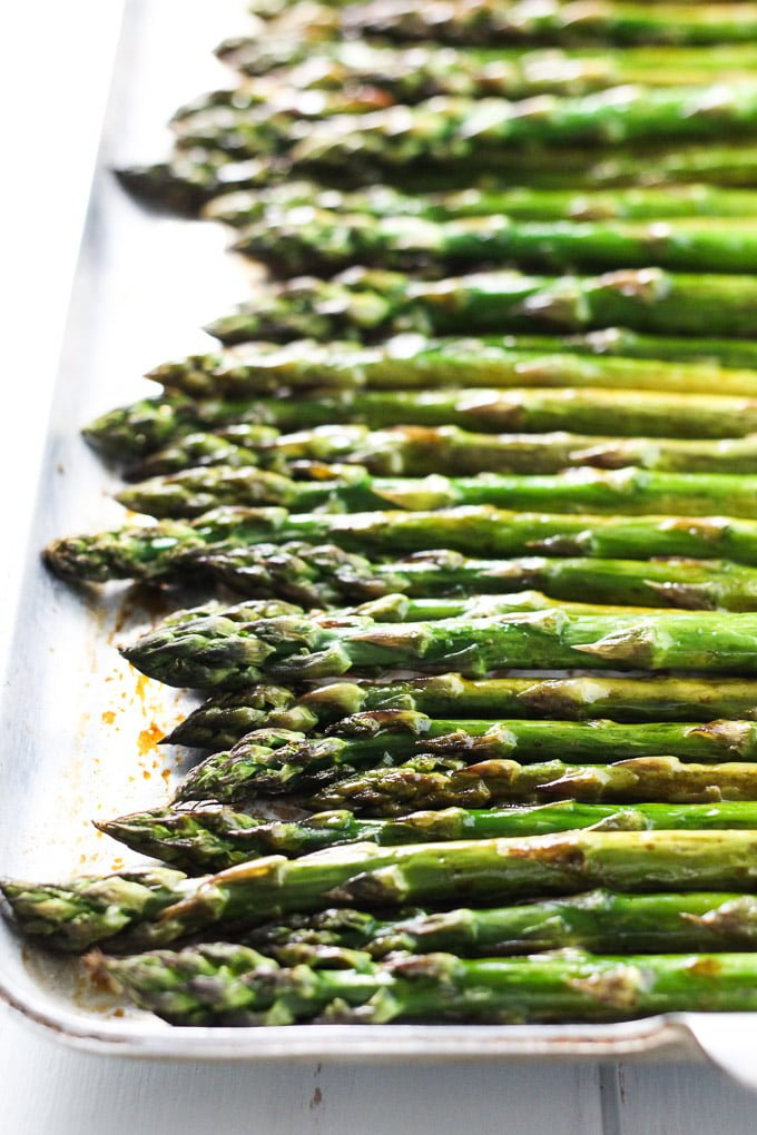 Roasted asparagus with balsamic vinegar on a baking sheet.
