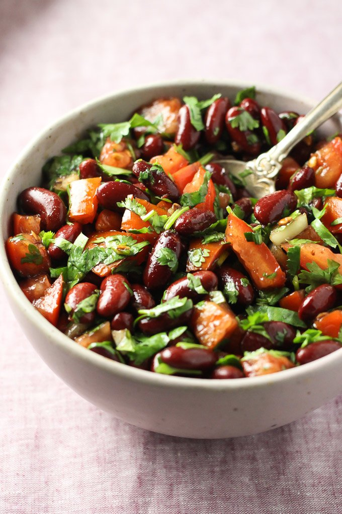 Red bean salad with tomatoes and fresh herbs in a bowl.