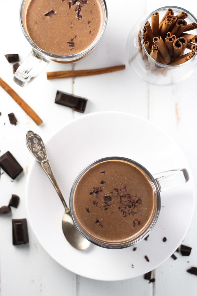 Hot chocolate in mugs, chocolate pieces, and cinnamon sticks on white background.