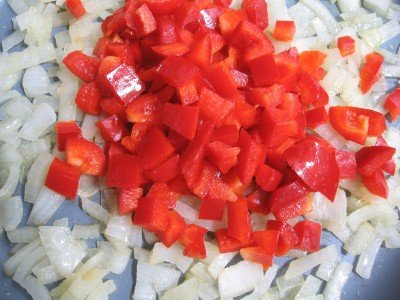 Onion and bell peppers in a frying pan.