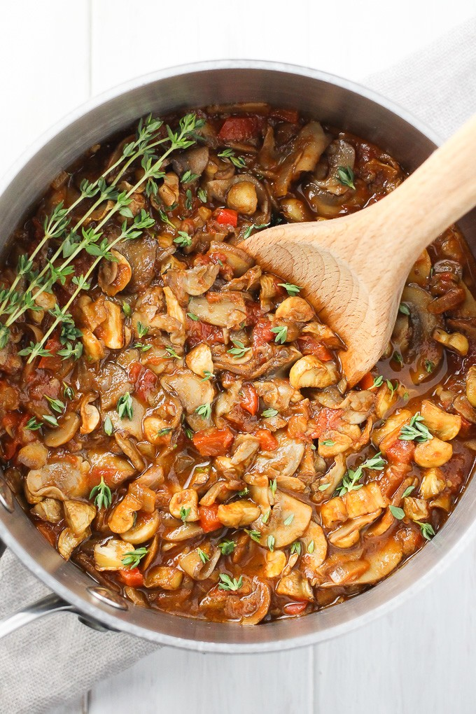Vegan mushroom goulash in a pot garnished with thyme. Top view.