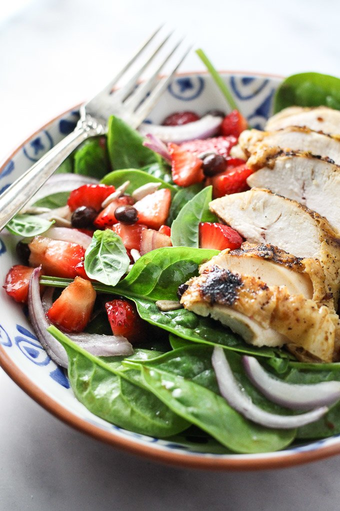 Spinach salad with chicken and strawberries in a bowl.
