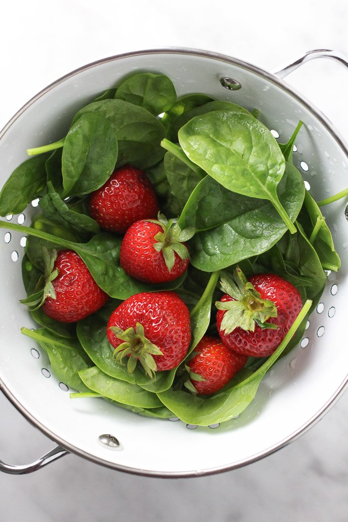 Spinach and strawberries in a white colander.