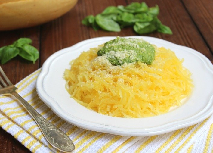 Spaghetti squash on a plate with a silver fork to the left.