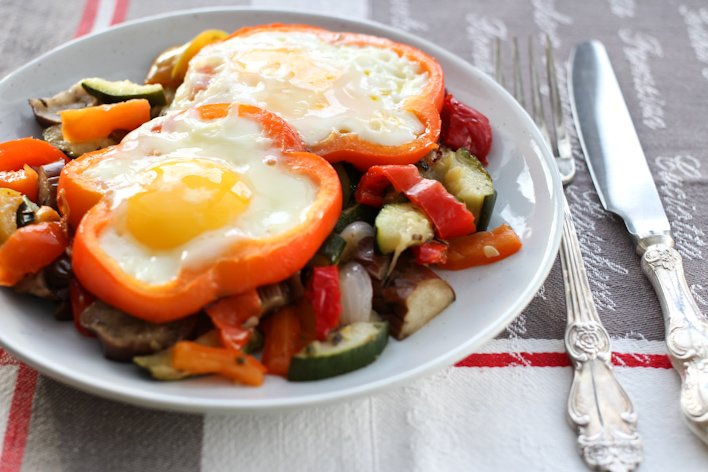 Sunny side eggs with vegetable served on a white plate with a fork and knife to the right.