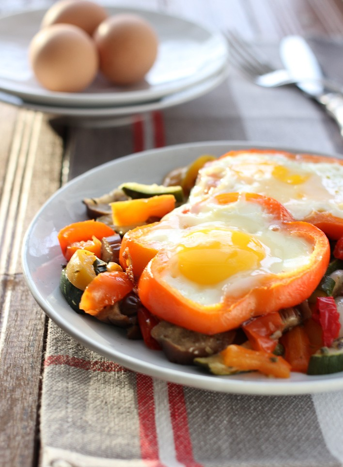 Sunny side up eggs with vegetables served on a white plate.