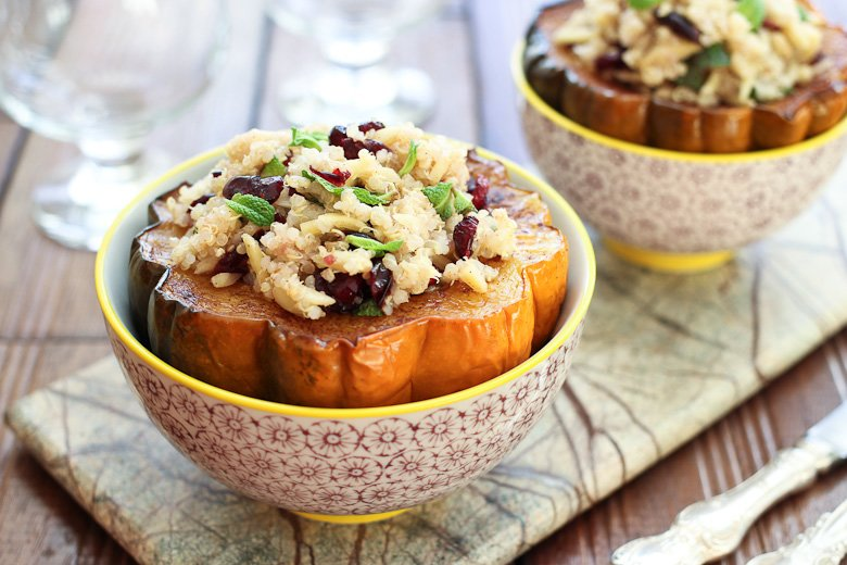 Roasted acorn squash seeds stuffed with quinoa salad, served in bowls.