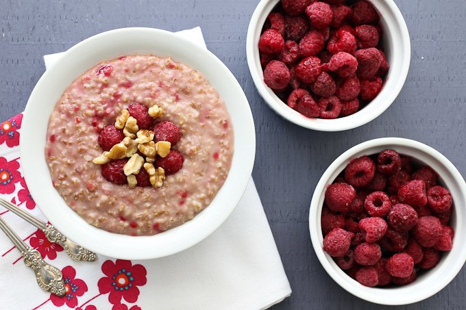 Raspberry steel-cut oats in a bowl and two bowls with raspberries.