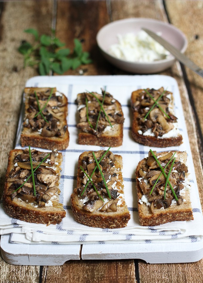 Goat cheese and mushroom crostini on a wooden board. Garnished with chives.