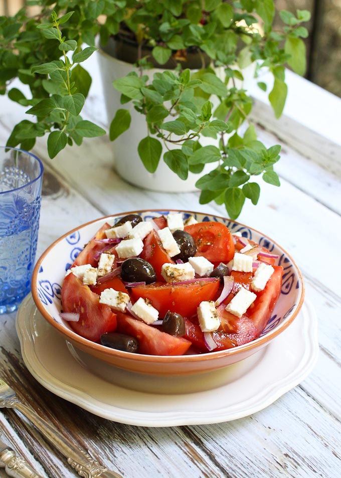 Mediterranean tomato salad in a bowl. Oregano plant in the background.