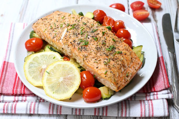 Roasted salmon with sauteed zucchini and tomatoes served on a white plate.