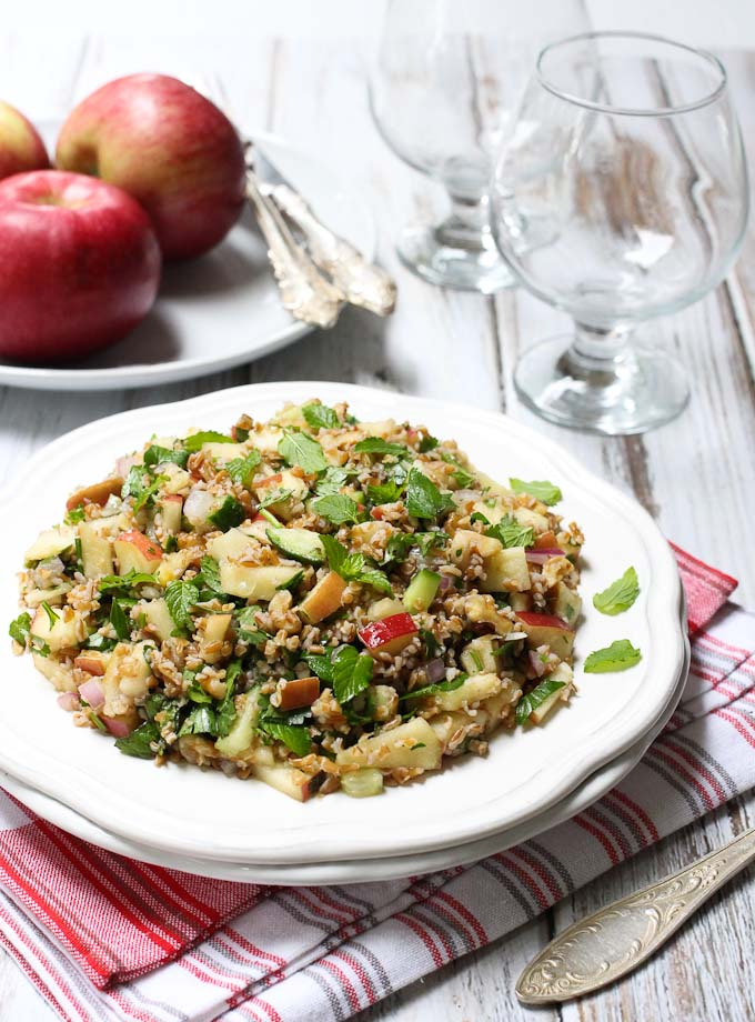 Tabbouleh with apples and walnuts on a white plate. Apples in the background.