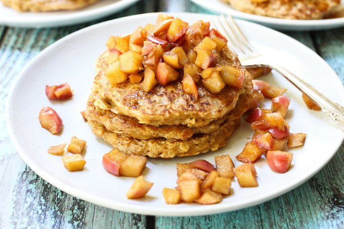 Oatmeal pancakes with apple topping. Served on a white plate.