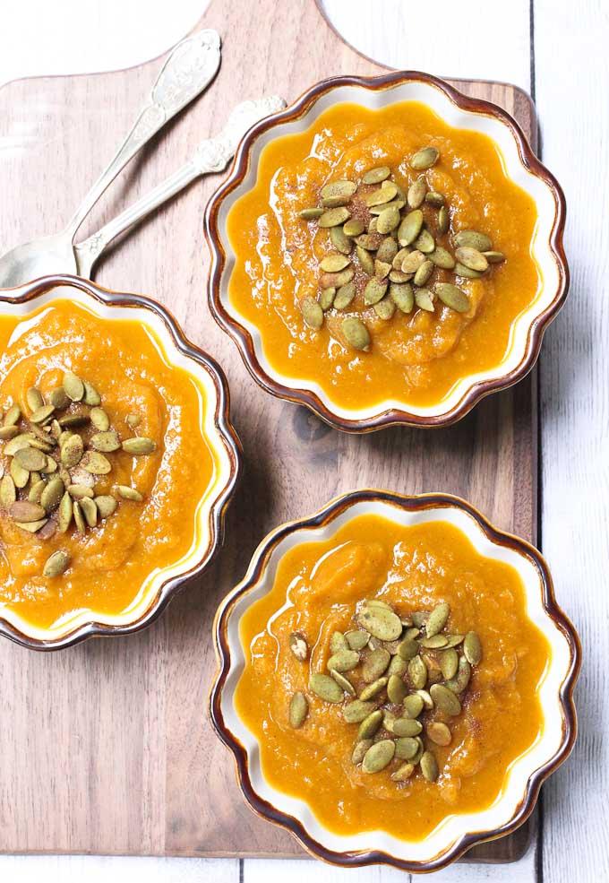Pumpkin appetizer soup in ramekins. Garnished with pumpkin seeds.