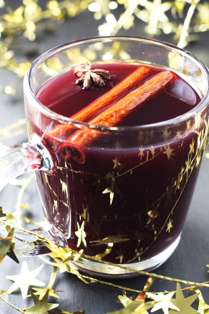 Close up of red Gluhwein in a mug decorated with cinnamon sticks and star anise.