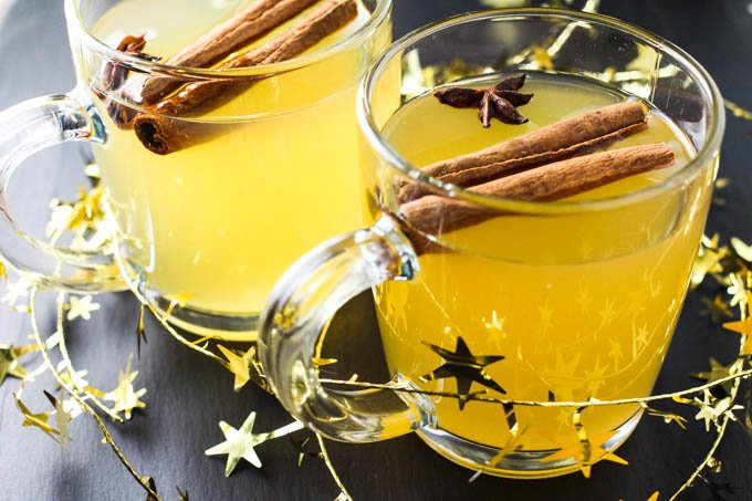 White Gluhwein in mugs garnished with anise stars and cinnamon sticks.