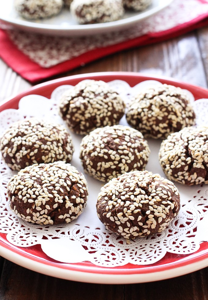 Chocolate cookies with sesame seeds on a red plate.