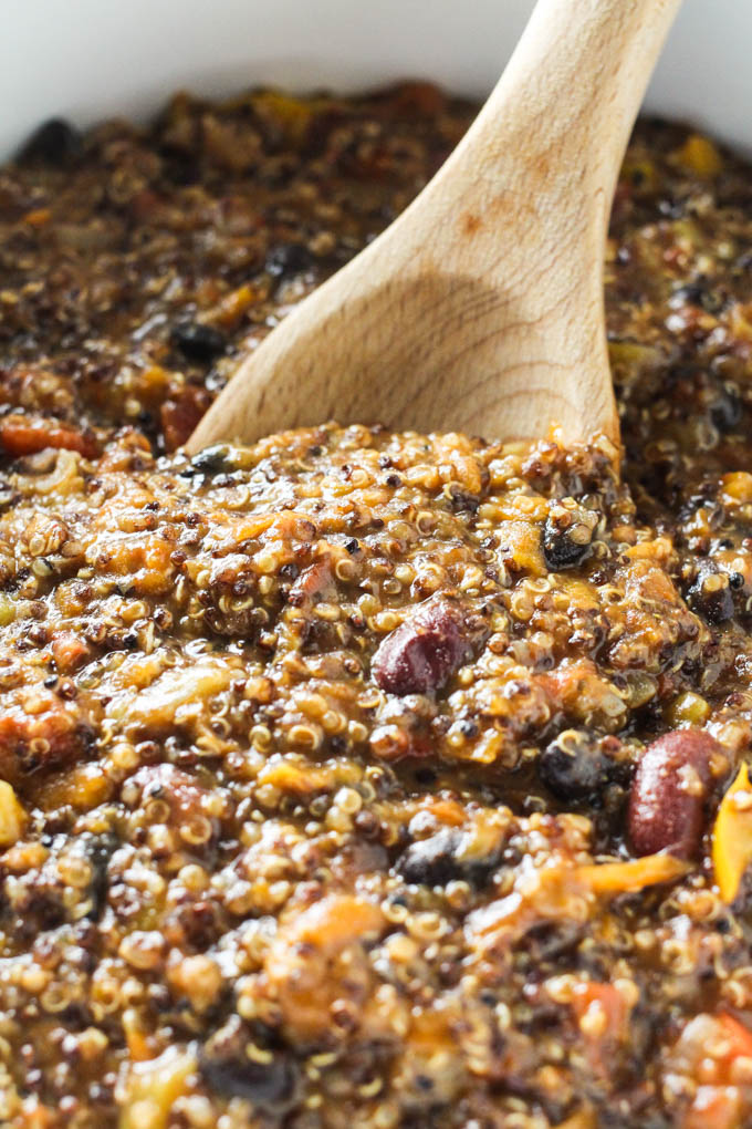 Quinoa chili being mixed with a wooden spoon.