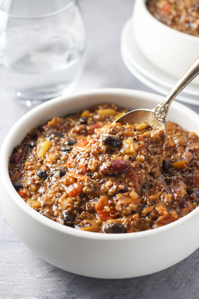 Quinoa chili being scooped with a spoon out of a bowl.
