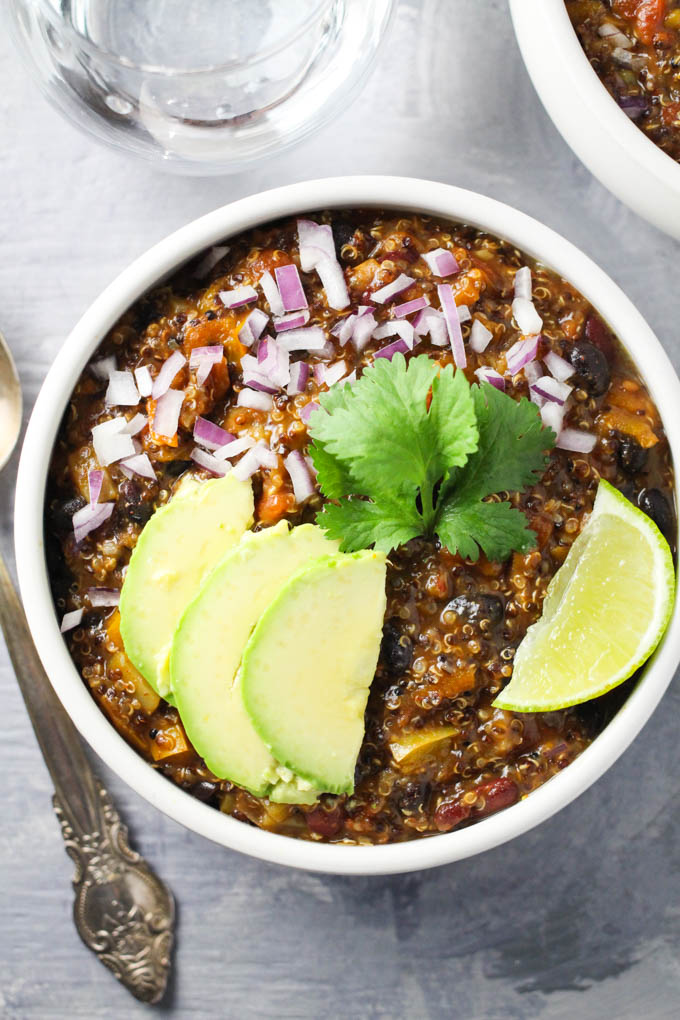 Quinoa chili in a bowl garnished with red onion, avocado, cilantro, and lime.