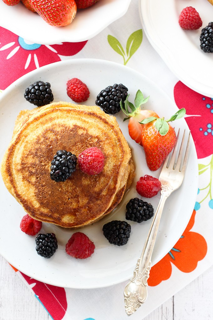 Spelt buttermilk pancakes on a white plate, garnished with berries.