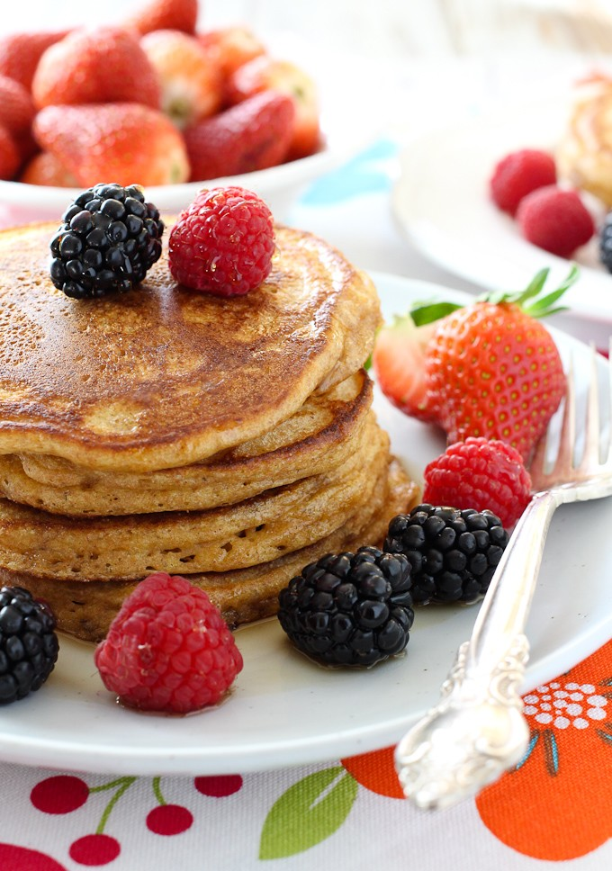Spelt buttermilk pancakes on a white plate, garnished with berries and maple syrup.