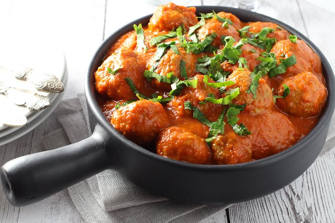 Meatballs in Red Pepper Sauce in a skillet.