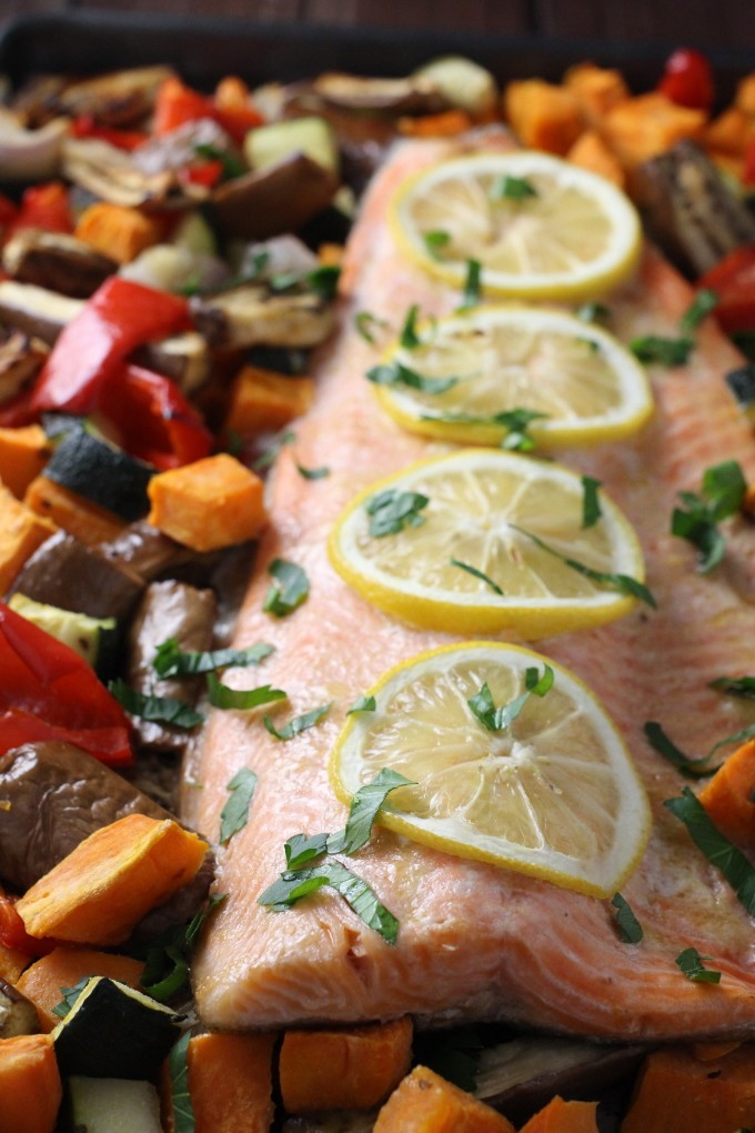 Baked rainbow trout with chopped vegetables, garnished with lemon slices.