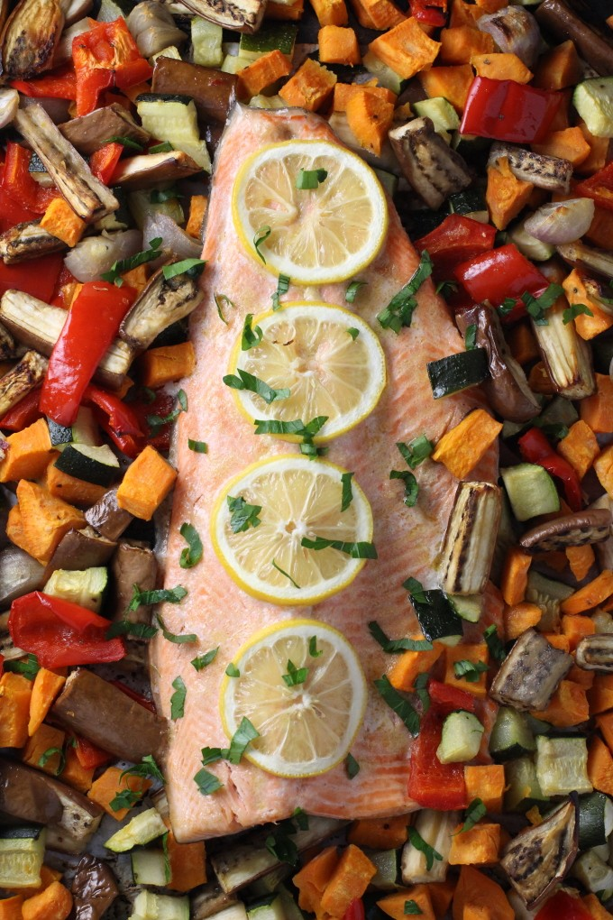 Baked rainbow trout with roasted vegetables, garnished with lemon slices.