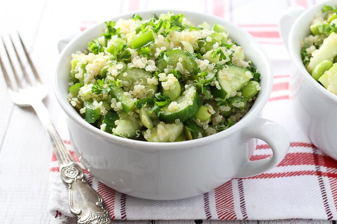 Green quinoa salad in a white bowl with a silver fork on the left.