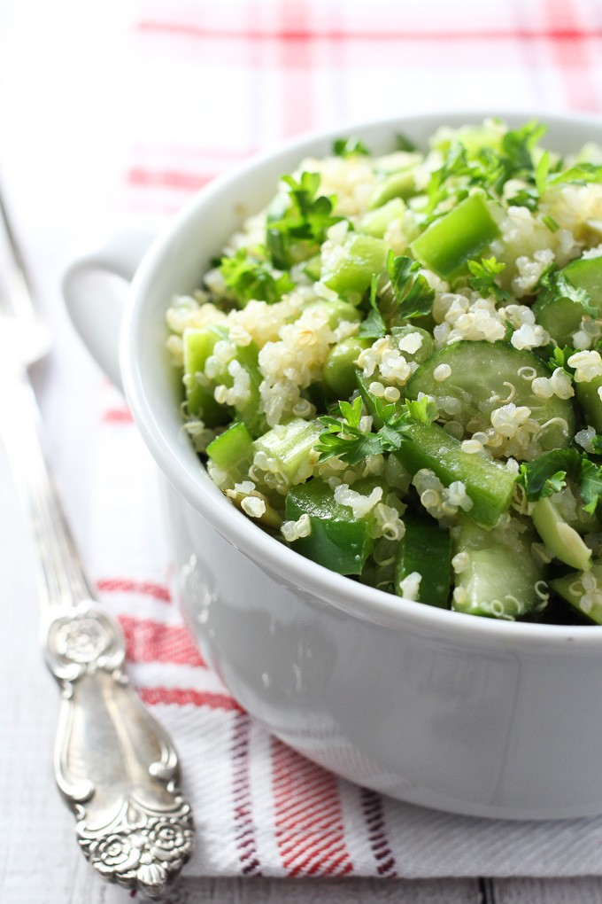 Green quinoa salad in a white bowl with a fork on the left.