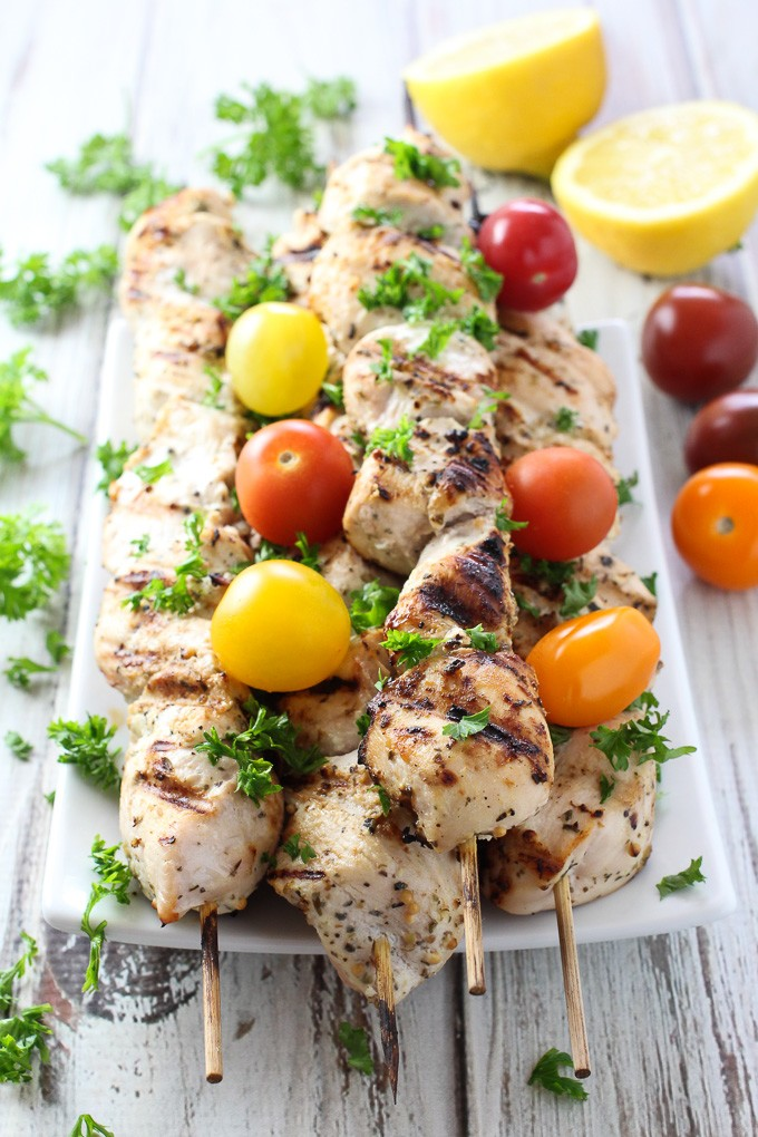 Yogurt marinated chicken kebabs on skewers, garnished with cherry tomatoes and chopped parsley.