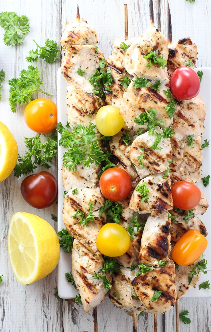 Grilled yogurt marinated chicken kebabs on skewers, garnished with cherry tomatoes and parsley. Top view.