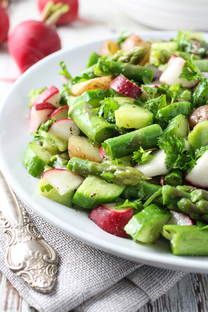 Potato salad with asparagus on a white plate.