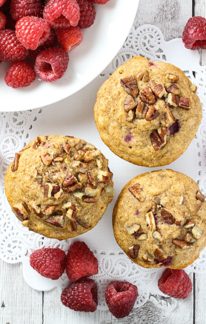 Top view of the spelt muffins and fresh raspberries which are arranged around them.