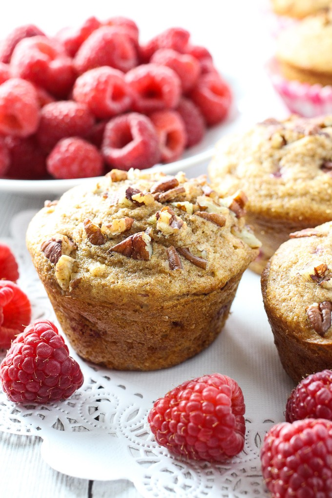 Spelt raspberry muffins on white background with whole raspberries around them.