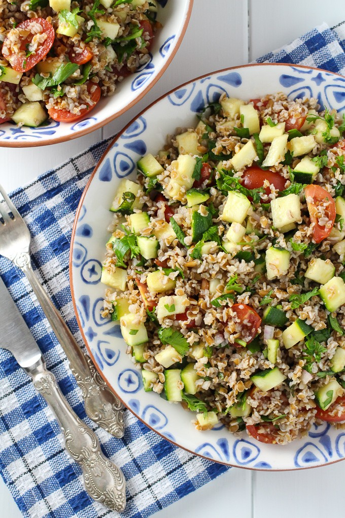 Zucchini tabbouleh salad on a plate with a fork and knife to the left. Top view.