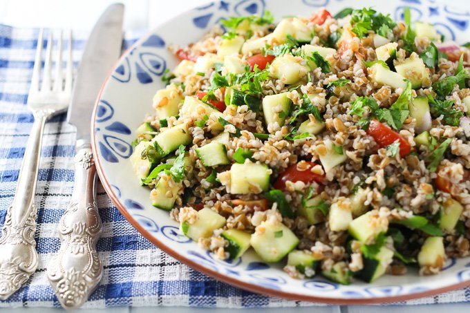 Zucchini tabbouleh salad on a plate with a fork and knife on the left side.