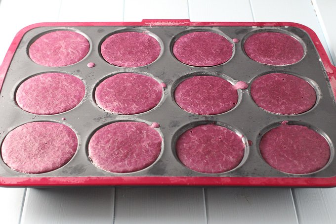 Blueberry frozen yogurt in a muffin pan.