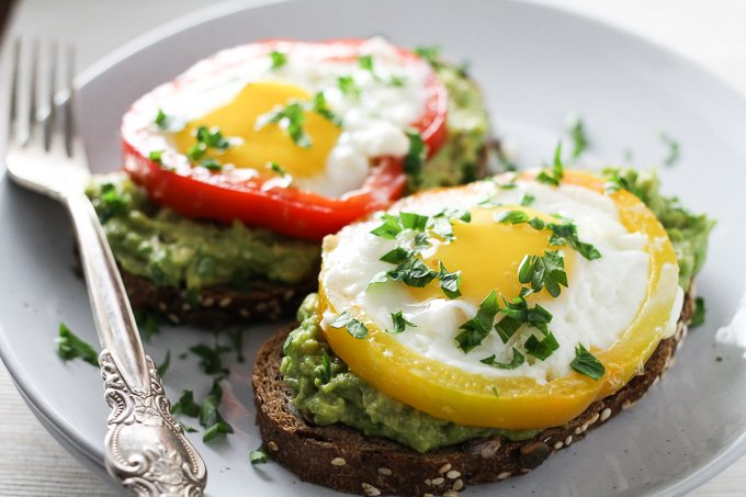Close-up side view of two egg avocado toasts on a white plate with a silver fork on the left.