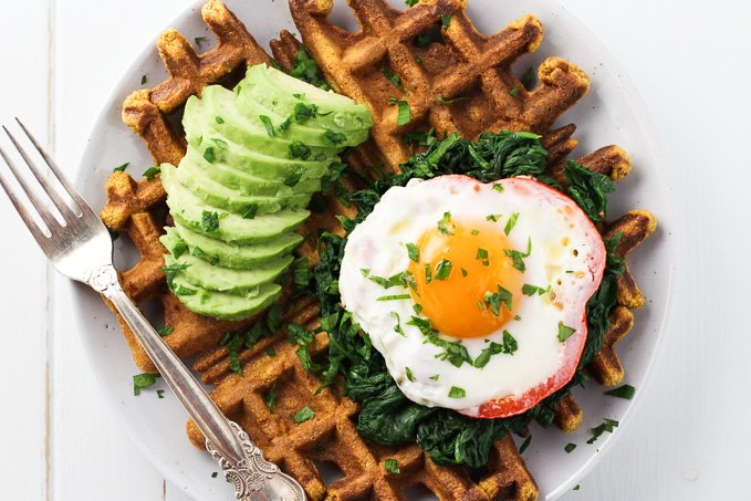 Top view of a sweet potato waffle topped with a fried egg, spinach and avocado. There is also a silver fork on the left.