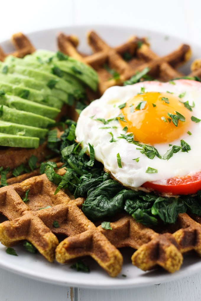 Close-up side view of a Sweet Potato Waffle topped with a fried egg, spinach and avocado.