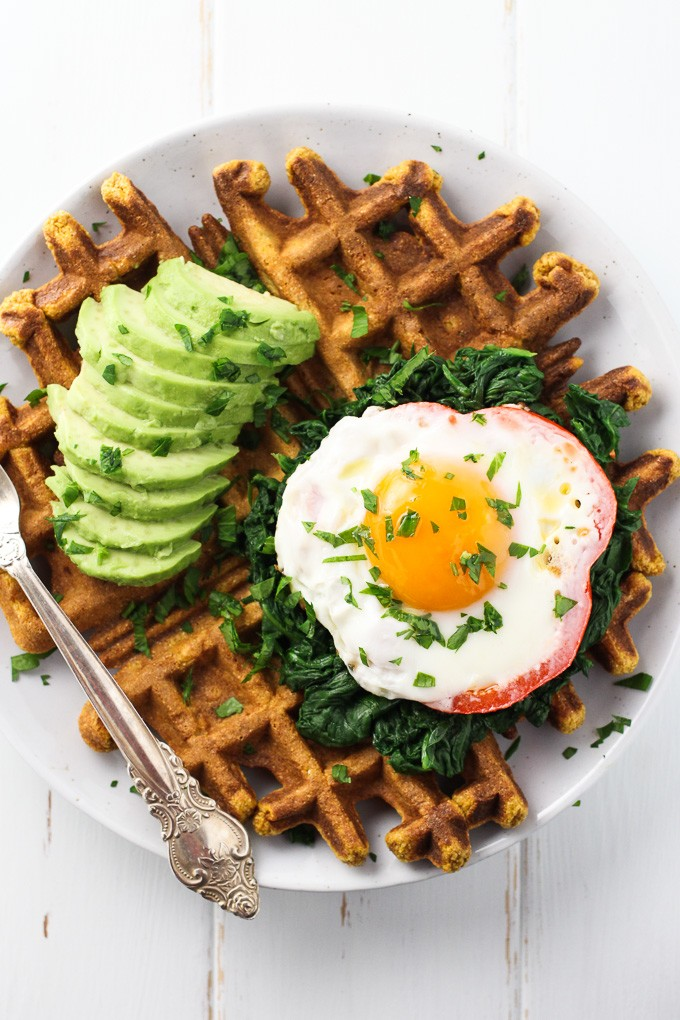 Top view of a Sweet Potato Waffle topped with a fried egg, spinach and a few avocado slices.