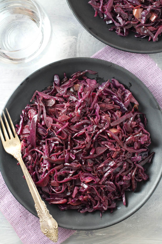 Top view of the German red cabbage on a plate standing on a purple napkin. A silver spoon on the left side.
