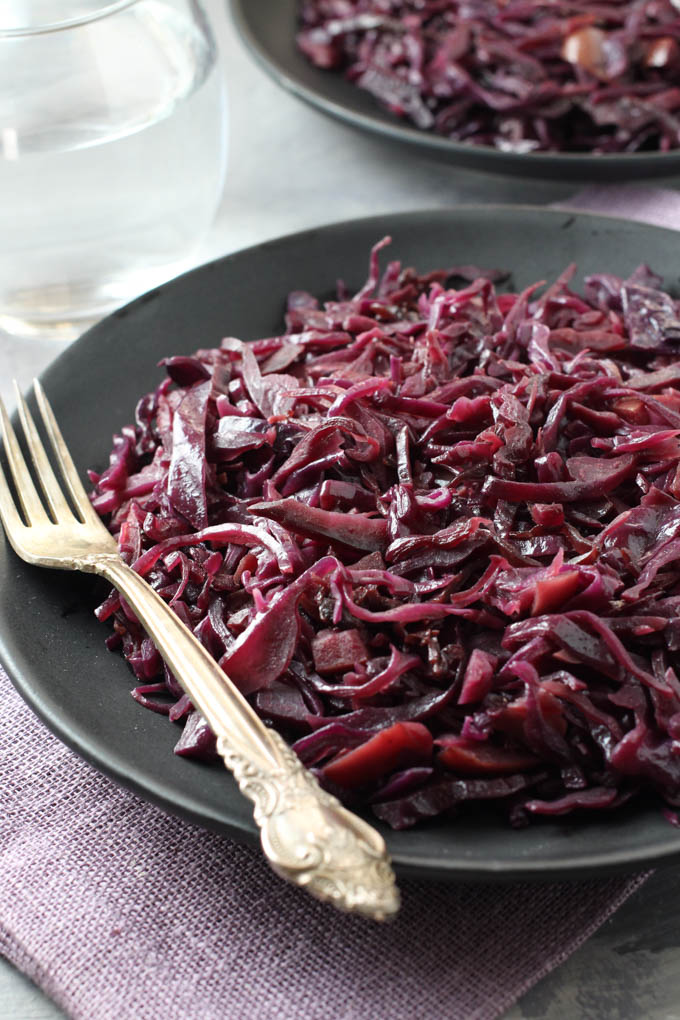 Braised red cabbage on a black plate with a silver spoon on the left side.