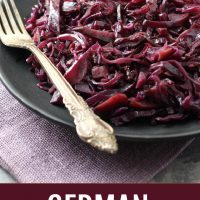 Braised red cabbage on a black plate with a silver spoon on the left side. Under the image, there is text saying German Red Cabbage with Apples.