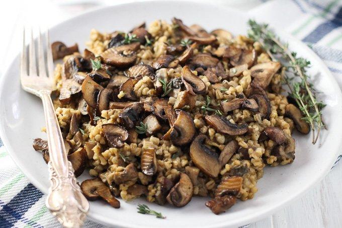 A close-up side view of the savory steel cut oats with mushrooms and thyme on a white plate with a silver fork on the left.
